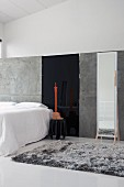 Minimalist gallery bedroom with grey flokati rug and large, full-length mirror against grey partition