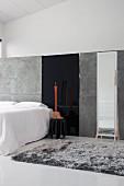 Minimalistisches Galerieschlafzimmer mit grauem Flokatiteppich und großem Standspiegel an grauer Trennwand