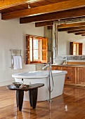 Designer bathtub in spacious bathroom with ethnic table and wooden washstand below wood-beamed ceiling