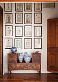 China vases on antique bench below collection of framed drawings on wall