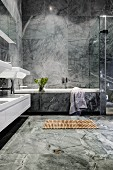 Luxurious bathroom with grey marble tiling and wooden duckboard bath mat in front of bathtub