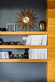 Collection of Murano glass ornaments and books on wooden shelves against grey wall below sunburst-shaped wall clock