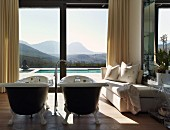 Luxurious bathroom with free-standing twin bathtubs and magnificent view of landscape