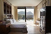 Bright bedroom with antique wooden furniture and splendid view of landscape through floor-to-ceiling glass wall