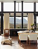 Schwarzer Kaminofen mit zwei Ofenrohren vor prachtvoller Bergkulisse in offenem Wohnraum mit rustikalem Esstisch und weissen Armstühlen