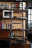 Wooden ladder leaning against tall, shabby chic wooden shelves; industrial window with view of cityscape in background