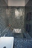 Spa atmosphere in narrow bathroom with blue and black mosaic tiles