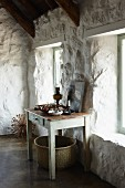 Vintage wooden table against whitewashed, rustic stone wall in pale room; large basket below table