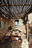 Rustic terrace with simple sunshade made from long bamboo poles and stone floor