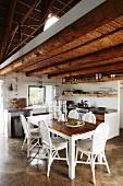 Offener Wohnraum mit einfacher Küche und Holztisch mit weissen Stühlen unter rustikaler Holzbalkendecke