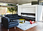 Two black leather sofas in modern living room with chrome arc lamp and open fireplace; garden terrace with pergola in background