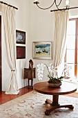 Orchideenschale auf rundem Holztisch; Malerei und Kunstobjekt in Zimmerecke