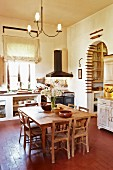 Rustic dining area in spacious kitchen-dining room; collection of rolling pins in arched doorway