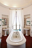 Round bathroom with bathtub in centre of room in front of French windows flanked by twin pedestal washbasins