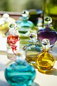 Collection of glass perfume bottles filled with fluids of various colours