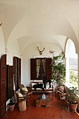 Armchairs and wood block table in spacious loggia with classical groin vaults