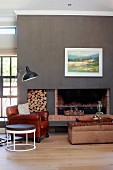 Round side table, leather armchair and retro standard lamp in front of open fireplace with firewood stacked in niche in wall painted dark grey
