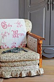 Traditional armchair with floral upholstery and embroidered antimacassar on backrest in front of farmhouse cupboard painted grey
