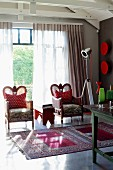 Two armchairs with red and white, polka dotted scatter cushions in front of glass wall and Oriental rug on polished concrete floor