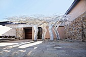 Four tree-shaped metal sculptures in courtyard with stone walls under blue sky
