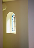 Small, arched, stained glass window