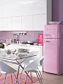 White kitchen with lilac wall and pink retro fridge; purple and orange rug below glass table
