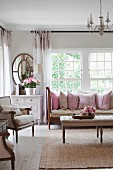 Touches of pink in comfortable living room with large soft scatter cushions on sofa and summery flower arrangements