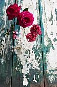 Rosen und Flieder auf verwittertem Holztisch