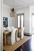 Long dining table and chairs with loose covers on pale sisal rug in front of large portrait of dog