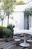Innenhof mit Holzdeck, Olivenbäumchen und blühendem Lavendel in großen Blumentöpfen; im Vordergrund eine weisse Sitzgruppe