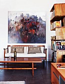 Modern oil painting over elegant wooden sofa; winding bookshelves on wall