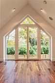 Interior of architect-designed house with parquet floor, large gable window element and view into garden