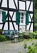 Summery atmosphere on terrace with garden table, garden chairs and bench in front of half-timbered house with green shutters