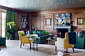 Walnut-panelled salon in blue and green combined with yellow 50s armchairs; silver reflective wallpaper on ceiling creates an illusion of height