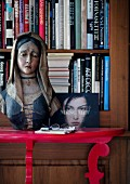 Painted, wooden bust of Madonna on red console table in front of bookcase