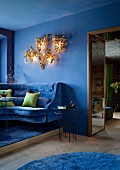 Blue lounge with velvet sofa and green scatter cushions; French club atmosphere provided by gilt, 70s chandelier with floral motif