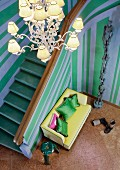 Chandelier and yellow sofa in grand stairwell with blue and green striped walls; totem pole artwork (stacked human forms) on marble floor