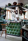 Old tiled stove in centre of rustic kitchen with old kitchen utensils on extractor hood