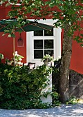 Sunny terrace with parasol adjoining renovated manor house with red facade and white door with latticed glass panels