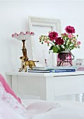 Bouquet of pink roses, antique bedside lamp and dog figurine on white-painted bedside table