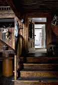 Former barn used as foyer - hunting trophies on wooden wall next to wooden steps leading to open door
