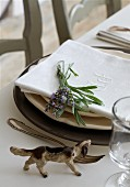Dog ornament on table next to place setting with sprig of lavender on linen napkin