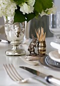 Ornamental, silver toothpick holder with hare figurine next to bouquet of white garden flowers in silver-plated vase on table