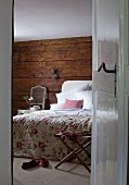 View through open door into bedroom with floral bedspread on bed against rustic wooden wall