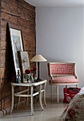 Corner of rustic room with wooden wall, table lamp and framed pictures on side table next to Rococo-style armchair with red and white checked upholstery