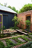 Landscaped pool and beds in courtyard with brick wall adjacent to house with corrugated metal cladding