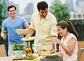 Young people setting table for barbeque in garden