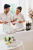 Young man & young woman preparing a buffet