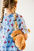 Girl in nightshirt carrying teddy bear