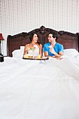 Couple in enormous double bed with breakfast tray
